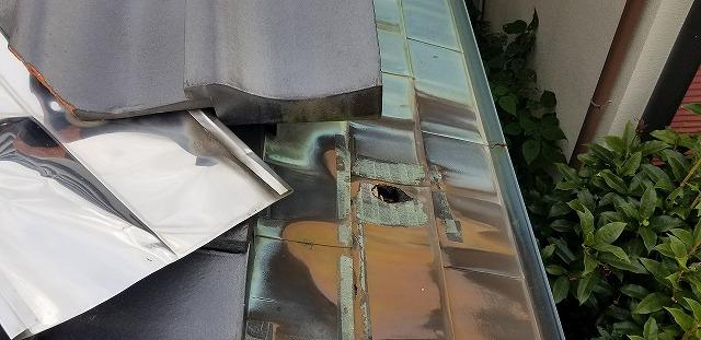 銅板に空いた大きな穴の写真