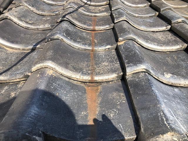 銅樋からの雨水による赤錆したいぶし瓦の写真