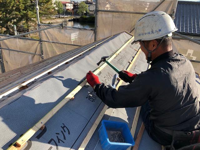 屋根に桟木を打っている写真