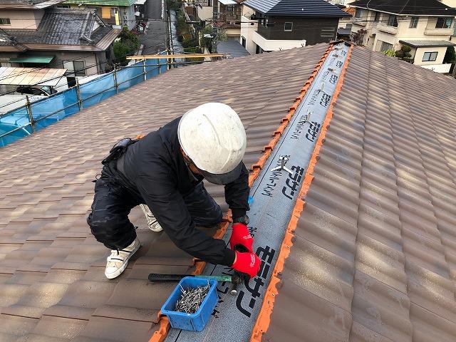 屋根棟部に強力棟を取り付けている写真