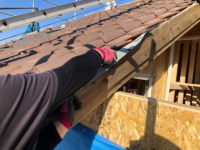屋根袖部のルーフィングを切っている写真