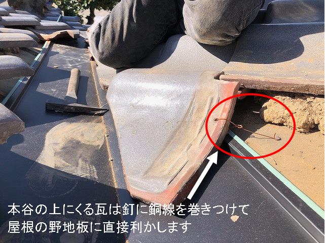 本谷の上にくる瓦を釘に銅線を巻き付けて施工している写真
