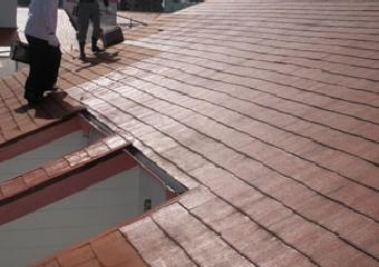屋根の下塗りをする風景